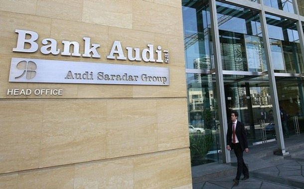 A customer walks past the main entrance of Bank Audi head office in Beirut